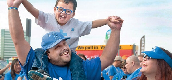 Man with young boy sitting on his shoulders as women looks on at Autism Speaks walk