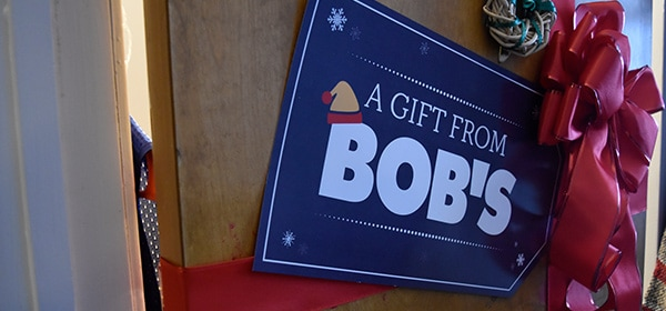 Oversized gift tag that reads A Gift From Bob's on the front of a door with a big red ribbon