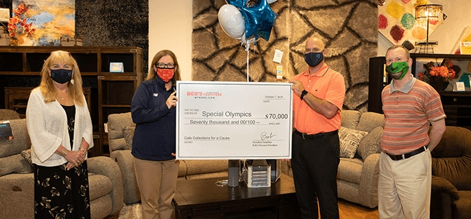 Several people standing in Bob's store to present large check to Special Olympics for $70,000.